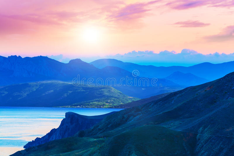 Scenic sunset in mountains. Scenic summer evening sunset in mountains landscape with sea coast royalty free stock image