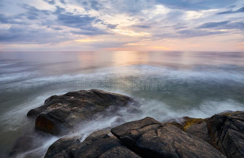 Scenic sunset over water seen from rocky shore royalty free stock photography