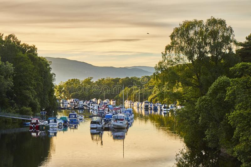 Scenic sunset view of Balloch harbour near Loch Lomond with floating boats reflected in river Leven, Scotland, United Kingdom. stock image