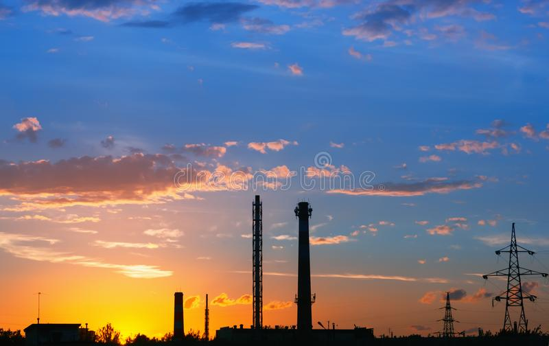 Industrial landscape with silhouettes of towers against the oran royalty free stock photography