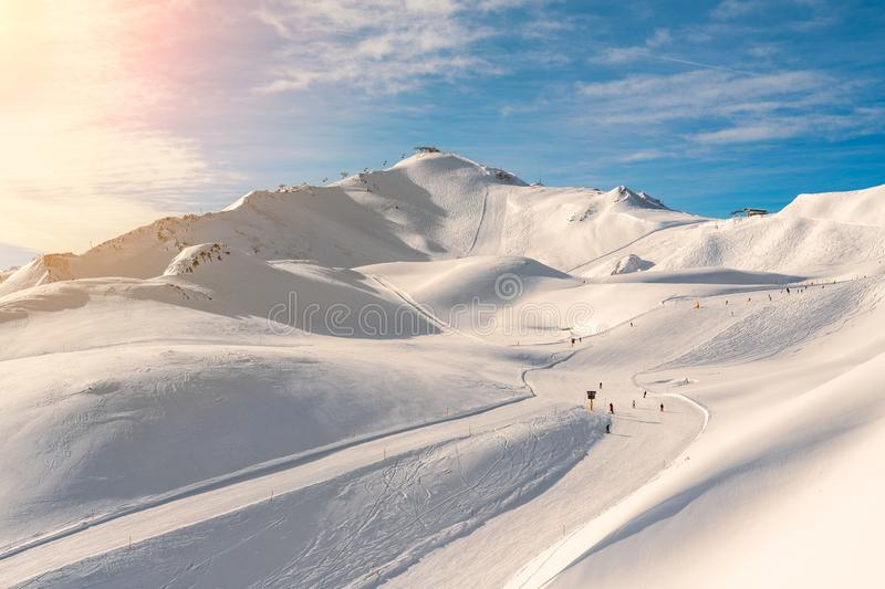 Scenic valley of hilghland alpine mountain winter resort on bright sunny day. Wintersport scene with people enjoy skiing stock image