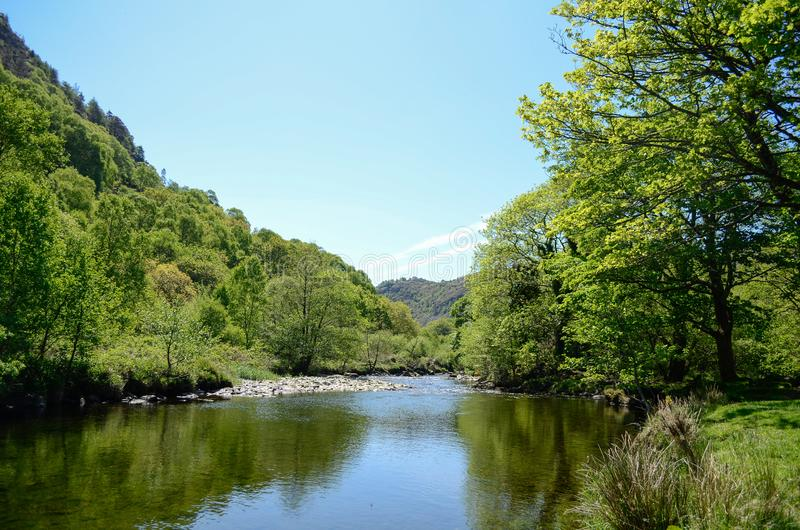 A scenic sunlit view along a calm river among green trees and under blue sky. A sunlit view along a river in Snowdonia, with calm waters running between rocks stock images