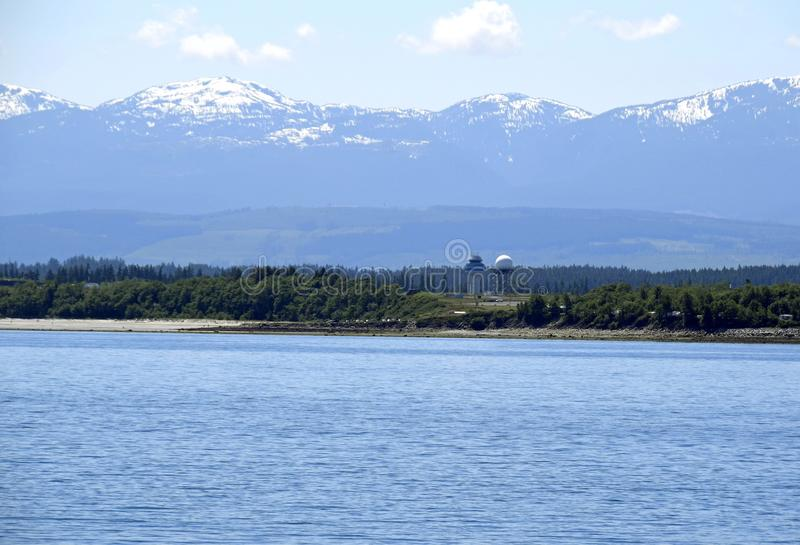 Comox airport tower and the Strathcona Mountain range in the background, Vancouver Island. Scenic view along the shoreline near Comox with view of the Comox royalty free stock image