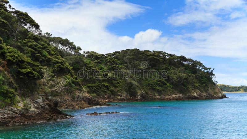 Coastal landscape in the Bay of Islands, New Zealand. A scenic view in the beautiful Bay of Islands, New Zealand, as seen from a boat. Native forest reaches down royalty free stock images
