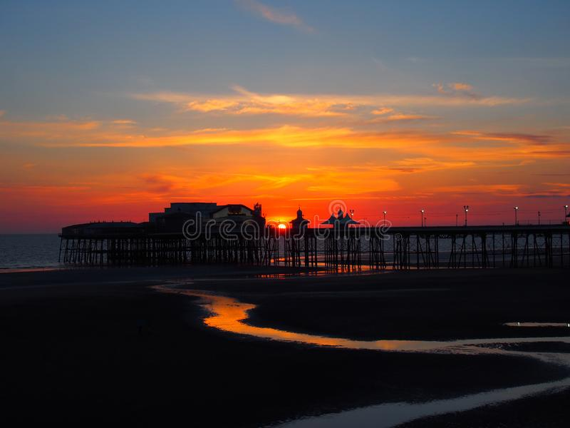 Scenic view of blackpool north pier in glowing red evening light at sunset with illuminated pink and yellow sky and clouds royalty free stock photos
