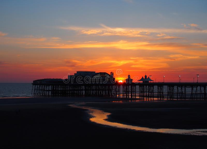 Scenic view of blackpool north pier in glowing red evening light at sunset with illuminated pink and yellow sky and clouds royalty free stock images