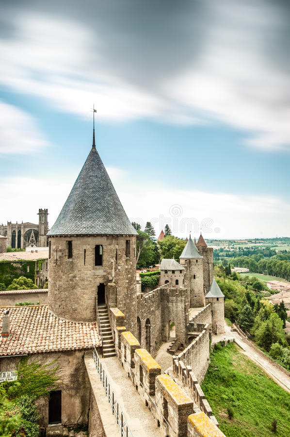 Scenic view of Carcassonne castle in France. Scenic view of ancient Carcassonne castle in France with grey stone walls and towers. Green trees and cloudy sky in royalty free stock photography