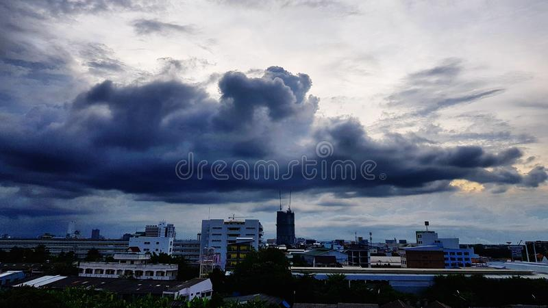 Scenic view of cityscape against storm clouds. Dark, sky, town, skyscraper, building, landscape, storm-clouds, rain, rainy, cloudy, weather, meteorology stock images