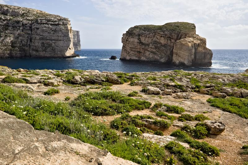 Scenic view of cliffs, fungus rock and blue ocean at dweira bay in gozo. stock photos