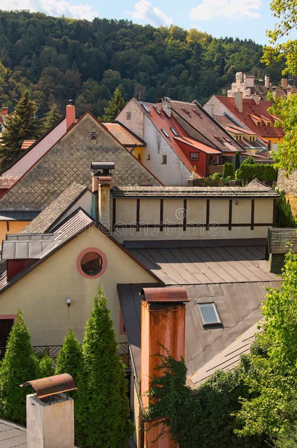 Scenic view of colorful tile roofs of old residential houses with the trees in the forest at the background. Summer day. Loket, Bohemia, Sokolov, Karlovarsky royalty free stock images