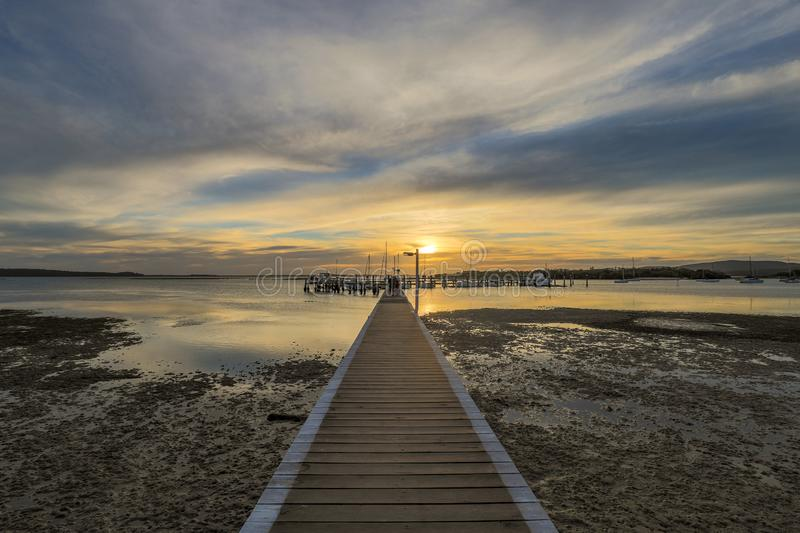Timber jetty leading to sun setting over ocean at low tide. Scenic view of colourful sunset over timber jetty and ocean at low tide royalty free stock photos