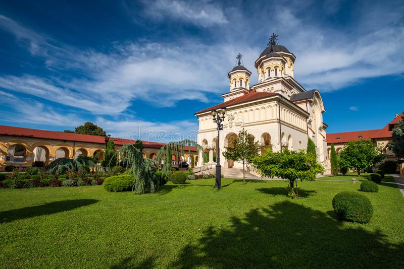 Scenic view of Coronation Orthodox Cathedral in Fortress of Alba Iulia, Romania. Green grass lawn of the temple complex and picturesque sky at sunny summer day stock photography
