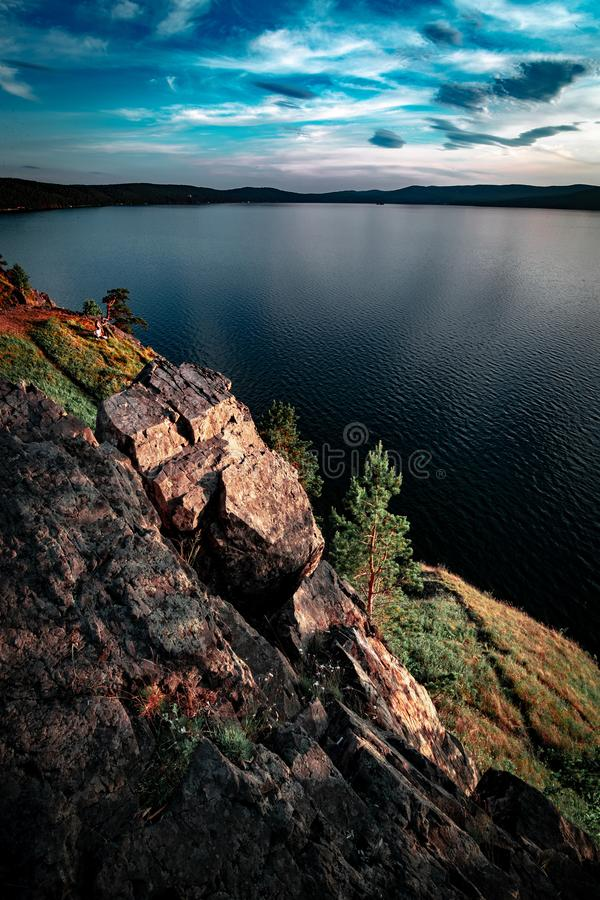 scenic view of dark blue mountain lake from rocky mountain with beautiful sky royalty free stock photo