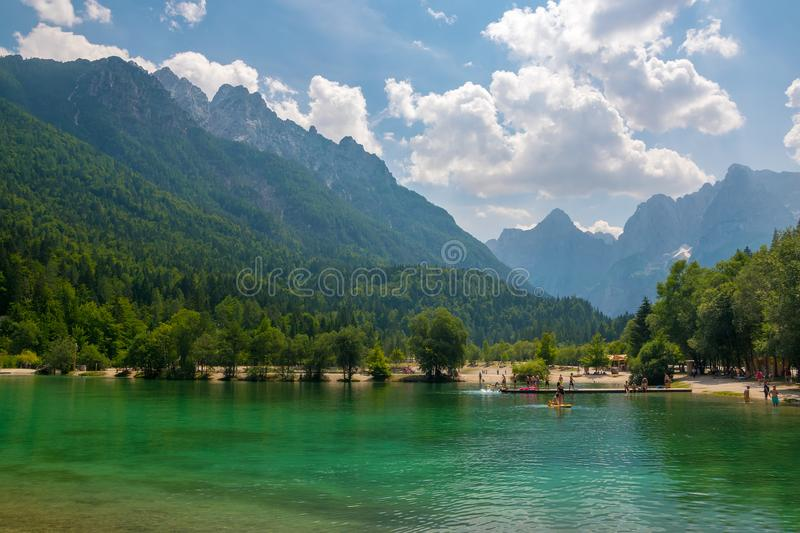 Scenic view of emerald water of Jasna lake near Kranjska Gora in Slovenia. Julian Alps in background stock photography