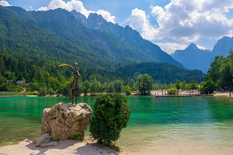 Scenic view of emerald water of Jasna lake near Kranjska Gora in Slovenia. Sculptures of Zlatorog - Goldhorn - a legendary creature in Slovenia culture in the royalty free stock images