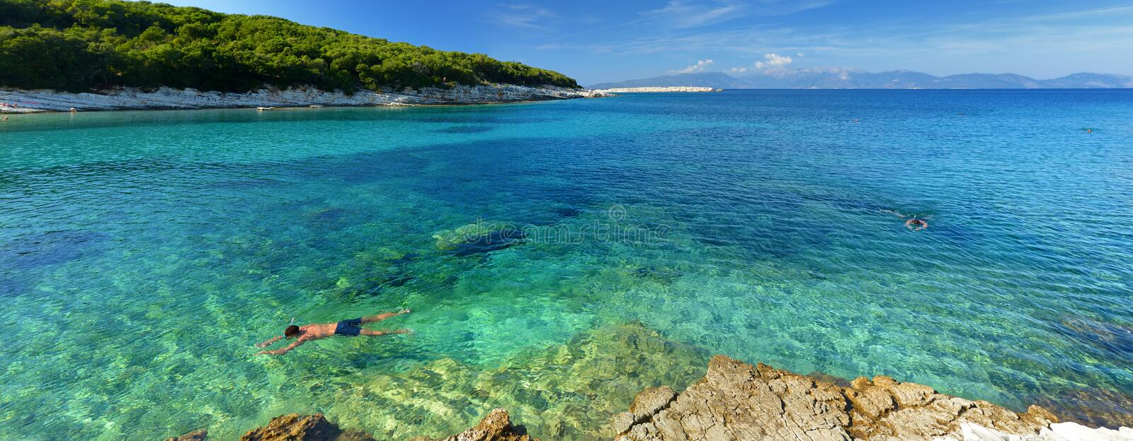 Scenic view of Emplisi Beach, picturesque stony beach in a secluded bay, with clear waters popular for snorkelling. Small pebble. Beach near Fiscardo town of royalty free stock photo