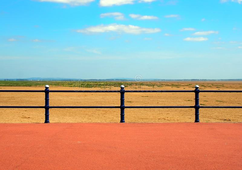 Scenic view from the end of the promenade at saint annes on the sea in lancashire with railings in front of the sandy beach with g. A scenic view of the end of royalty free stock photos