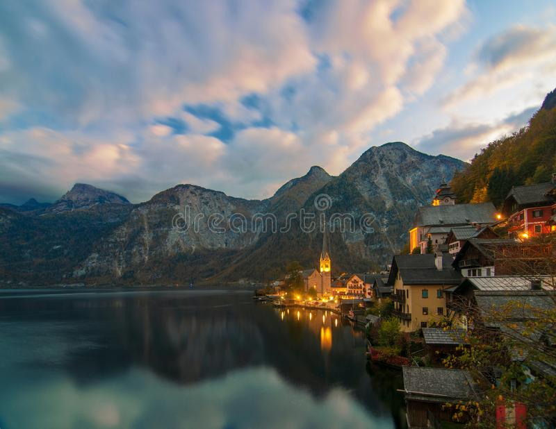 Scenic view of famous Hallstatt mountain village in the Alps under picturesque moving clouds after sunset, Austria stock photography