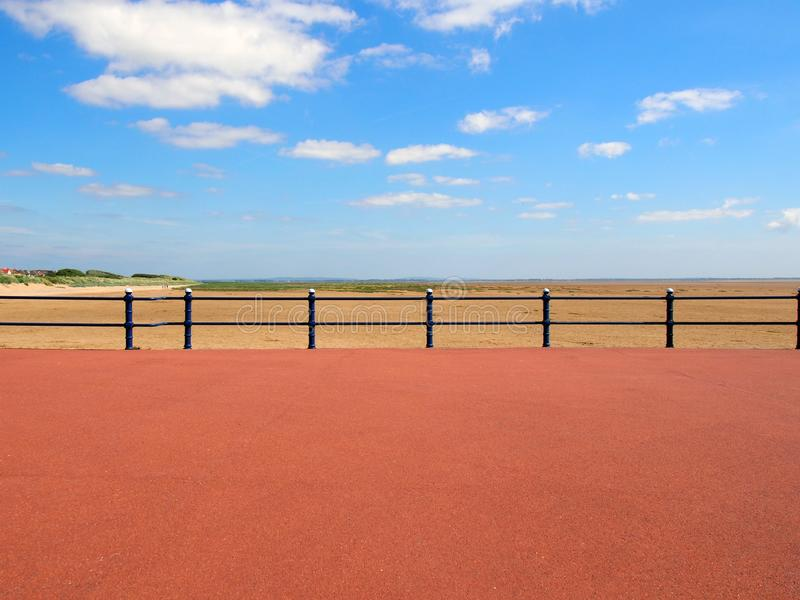 Scenic view form the end of the promenade at saint annes on the sea in lancashire with railings in front of the sandy beach. With grass covered dunes and the stock photos