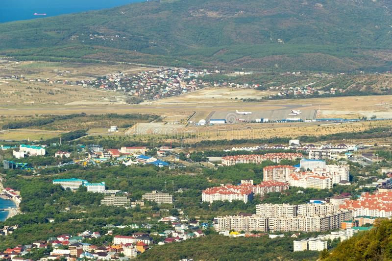 Scenic view of Gelendzhik resort city district from hill of caucasian mountains. Buildings, streets at the foot of the. Mountains. Airport runway strip and stock images