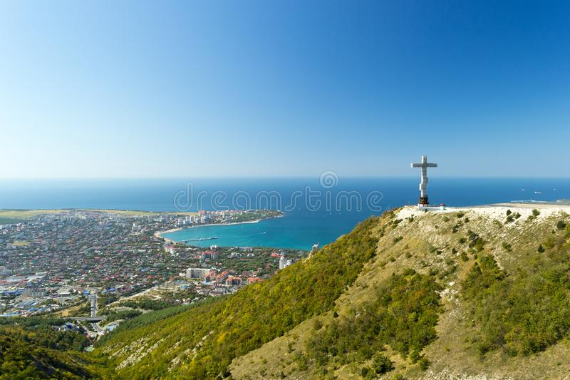 Scenic view of Gelendzhik resort city from hill of caucasian mountains. Worship cross monument with orthodox chapel in. Foundation on hill. City district, sky stock photography