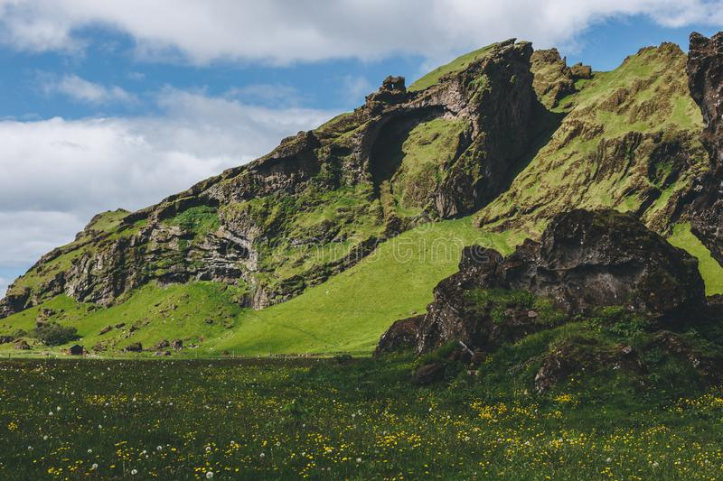 Scenic view of green meadow near mountain under cloudy blue sky. In Iceland stock photos