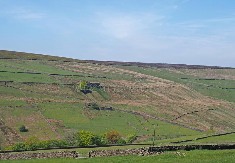 a scenic view of green meadows and stone walls underneath yorkshire hills ruined farmhouses and moorland on the old howarth road royalty free stock photography