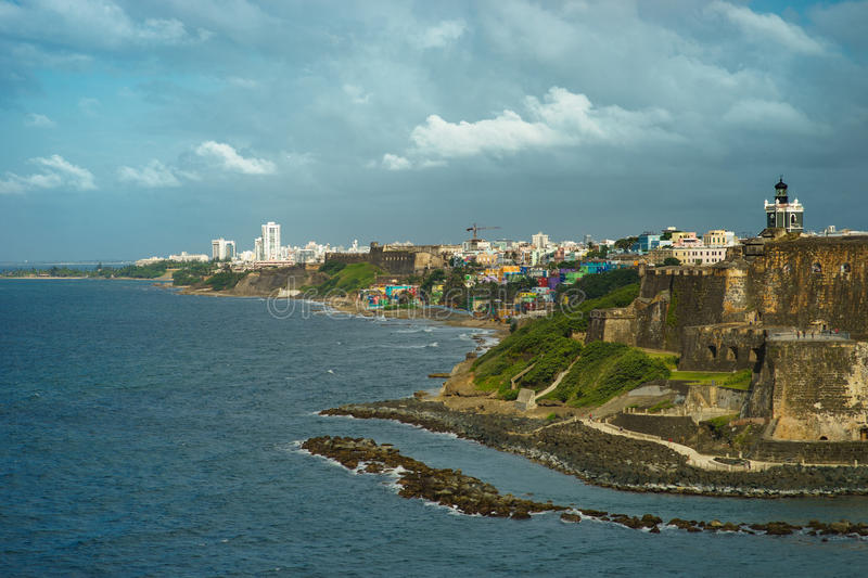 Scenic view of historic colorful Puerto Rico city in distance with fort in foreground royalty free stock image