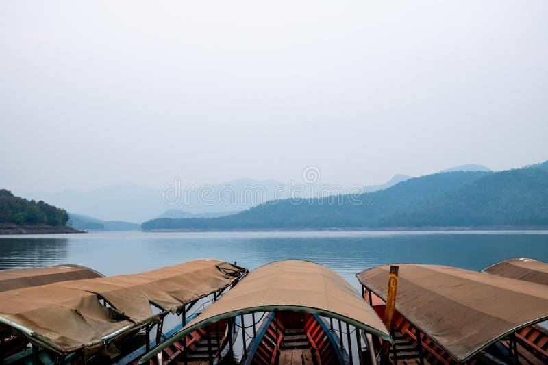 Scenic view of the lake with mountains on a cloudy day with row of long-tail boats mooring on foreground. stock photography