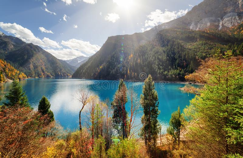 Scenic view of the Long Lake with azure water among fall woods. Beautiful view of the Long Lake with azure water among colorful fall woods and mountains in stock photography