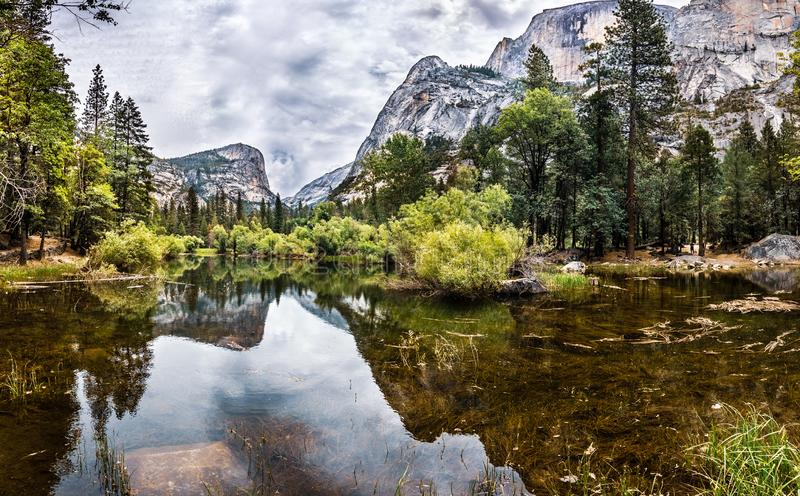Scenic view of Mirror lake, along Tenaya Creek; Half Dome and surrounding mountain ridges reflected in the shallow, calm waters of. The lake; Yosemite National stock photo