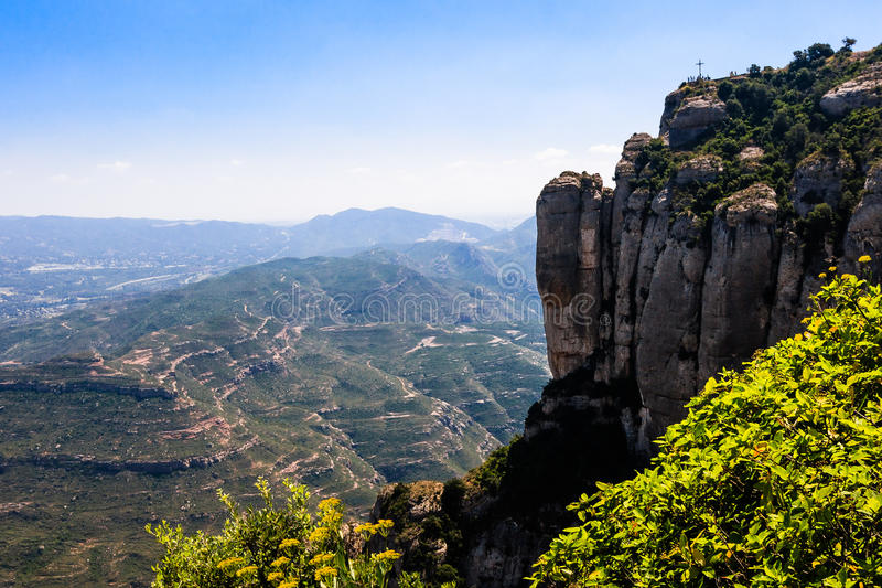 Scenic view with mountains. A beautiful view from Montserrat mountains with an iron cross and people on the top of the mountain royalty free stock photography