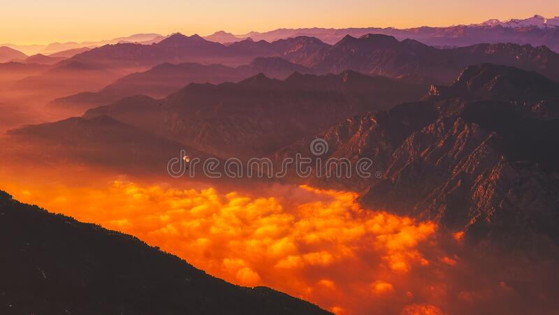 Scenic View of Mountains Against Dramatic Sky at Sunset stock photography