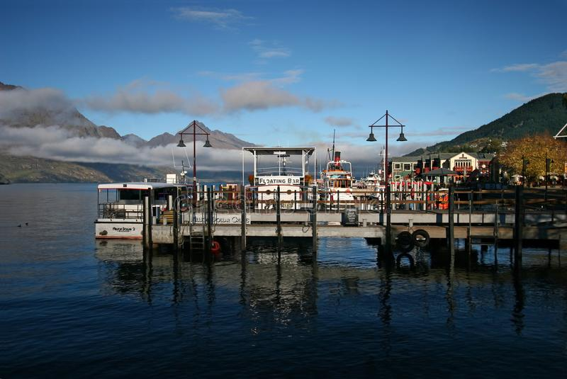 Scenic view of mountains with low clouds and boats moored to piers in small town. Waterfront docks on Lake Wakatipu, Queenstown, New Zealand royalty free stock images