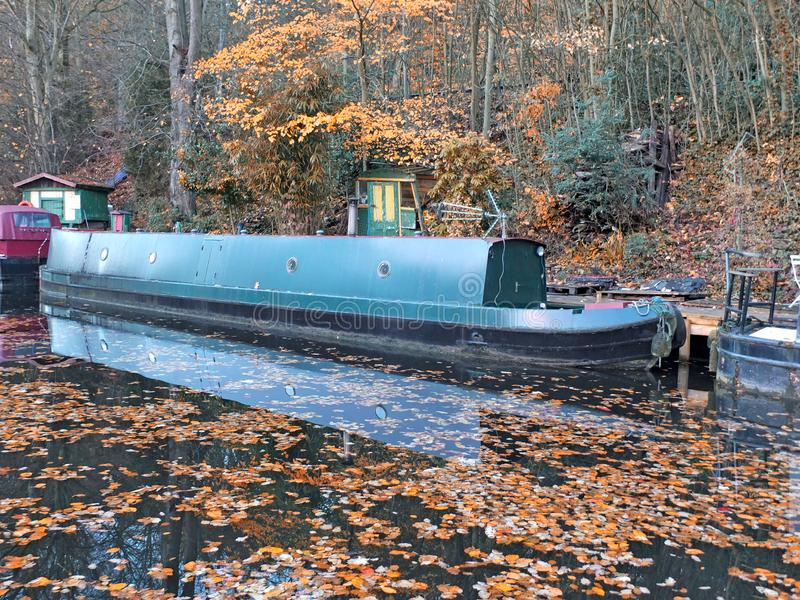 Scenic view of narrow boats in a canal surrounded by golden fallen autumn leaves with reflections on the water and forest trees stock photo