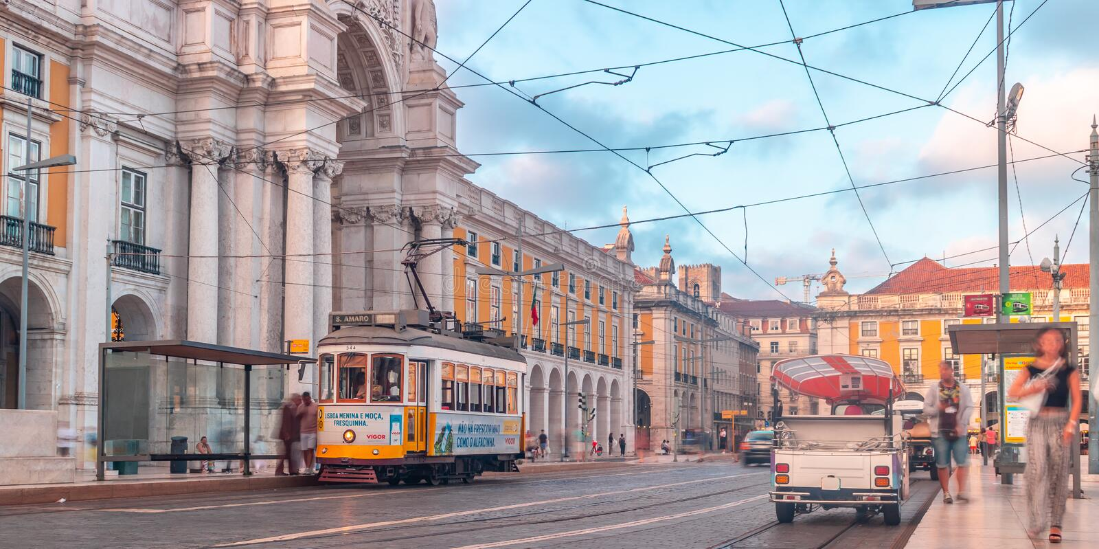 Scenic view of praça do comércio with Arco da Rua Augusta in frame. A tram waiting in its station beautiful blue sky and people moving  around And people royalty free stock images