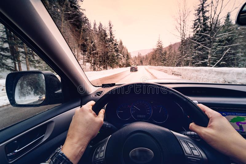 Scenic view of a road with snow covered landscape while snowing in winter season - view from the car. POV, first person view shot stock images