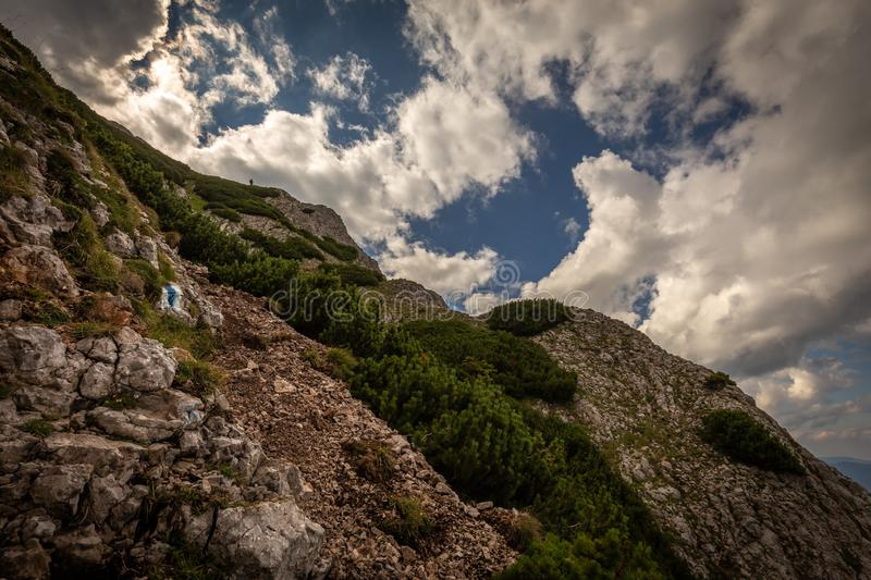 Scenic view on rocky route Nandsteig from Puchberg to Kaiserstein on Rax plateau. Schneeberg masif with dramatic cloudy sky and pine trees, Raxalpe, Lower royalty free stock photography