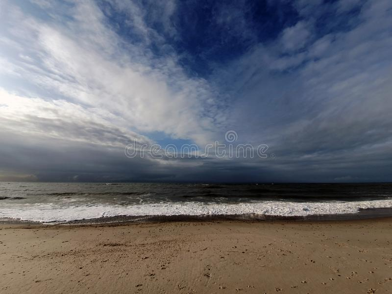 Scenic view of sea against sky. On a cloudy day with parts of blue sky stock image