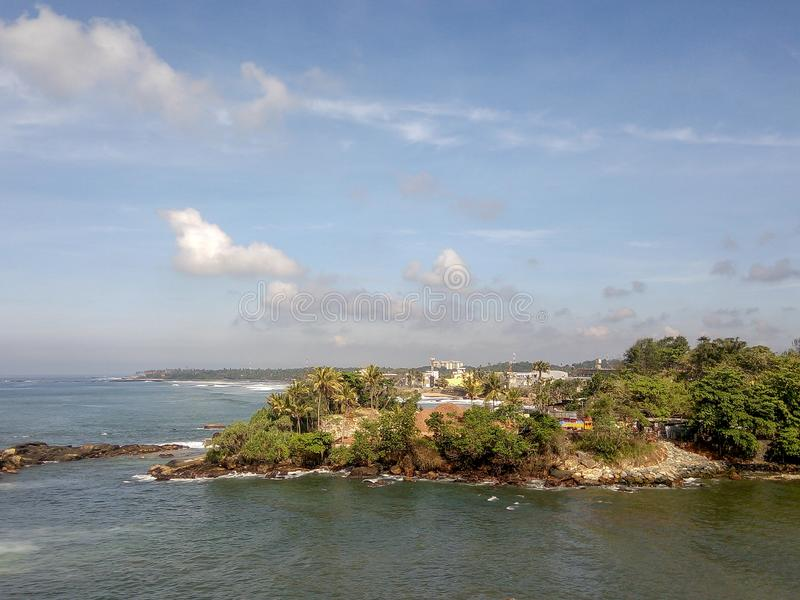Scenic view of the ocean against blue sky in Galle, Sri Lanka. Scenic view of the calm ocean against cloudy sky close the shore with green palm trees in Galle royalty free stock images