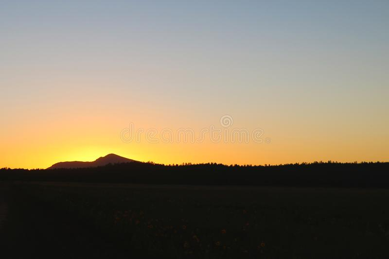 Scenic View Of Silhouette Mountains Against Orange Sky.  stock photo