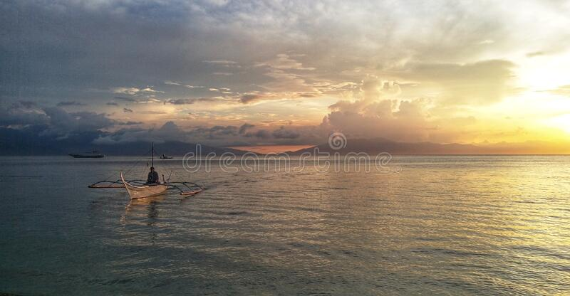 Small filipino fishing boat at sunset. Philippines. Scenic view of a small filipino fishing boat at sunset. Philippines royalty free stock photography