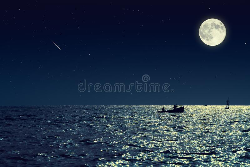 Scenic view of small fishing boat in calm sea water at night and stock photography
