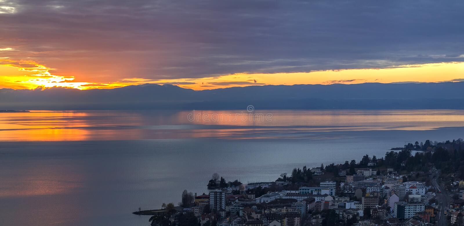 Scenic view of sunset over the Leman lake with yellow sky with clouds and Alps mountains in background, Montreux, Switzerland. stock photos