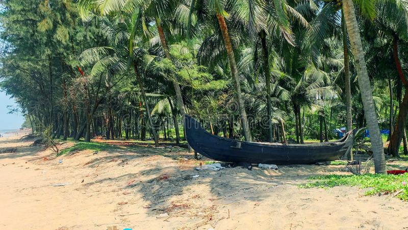 Scenic view to tropical beach  with  traditional fishing boat and beach huts on the coconut trees background in Kerala, South stock images