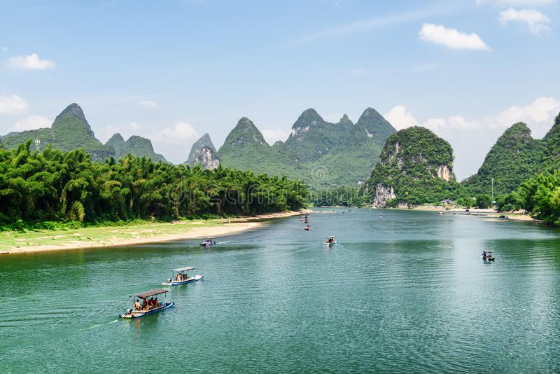 Scenic view of tourist motorized rafts on the Li River. (Lijiang River) with azure water at Yangshuo County, Guilin, China. Wonderful karst mountains are stock image