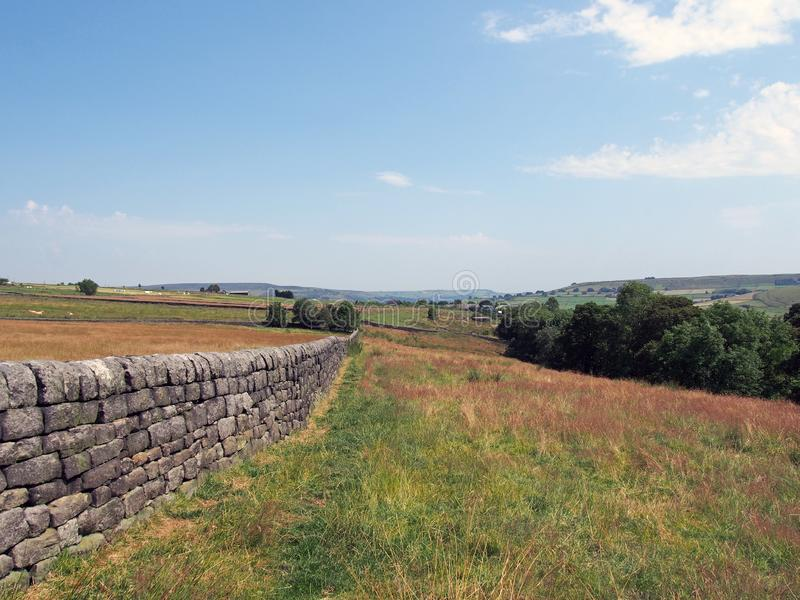 Scenic view of west yorkshire countryside with a long dry stone wall in summer meadows with hills farms and fields in the distance stock images