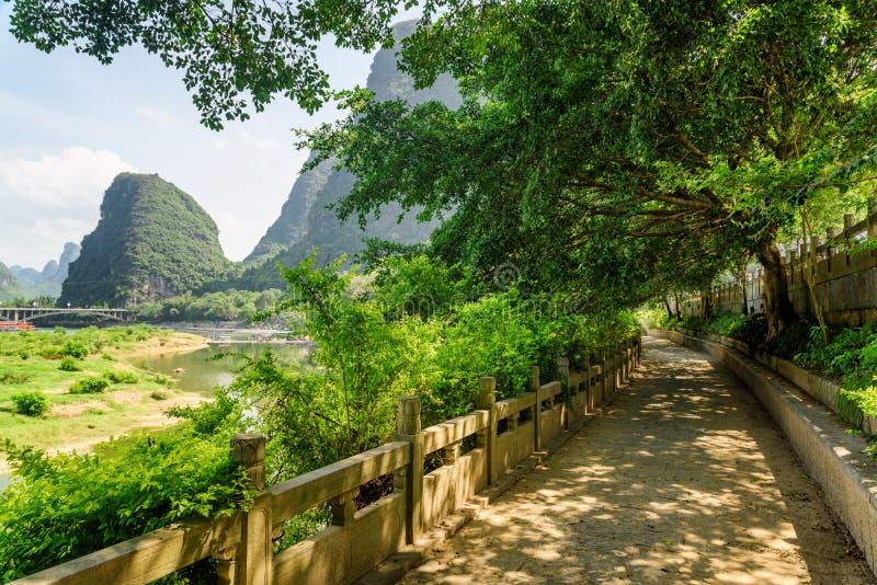 Scenic walkway among green trees along the Li River, Yangshuo royalty free stock photography