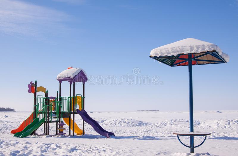 Scenic winter view of sun umbrella and colorful playground on deserted beach covered with snow. stock images