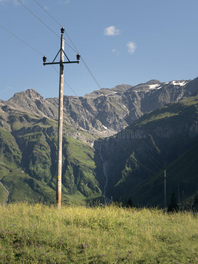 Sceniczna Alpejska skalista wysokogórska dolina Sportgastein w lecie z rzędem linie energetyczne i elektryczność słup fotografia stock